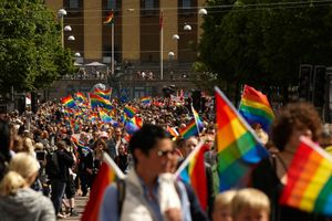 bilden visar ett folkhav med vajande regnbågsflaggor